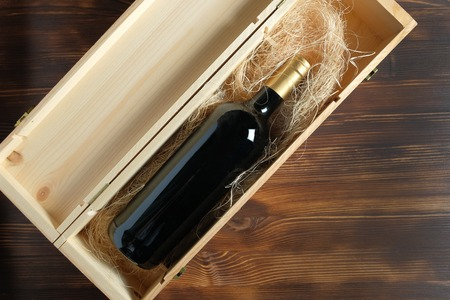 A dark expensive bottle of wine in a wooden box on a wooden background. Top view.