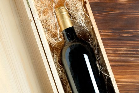 A dark expensive bottle of wine in a wooden box on a wooden background. Top view. Close up.