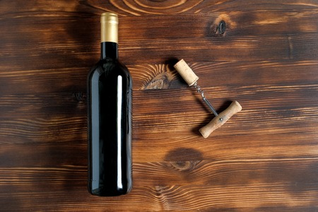 A dark bottle of wine next to a corkscrew and a twisted cork at the center on a wooden background. Top view. 스톡 콘텐츠