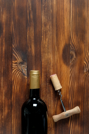 A dark bottle of wine next to a corkscrew and a twisted cork at the center side on a wooden background. Top view vertical with copy space. 스톡 콘텐츠