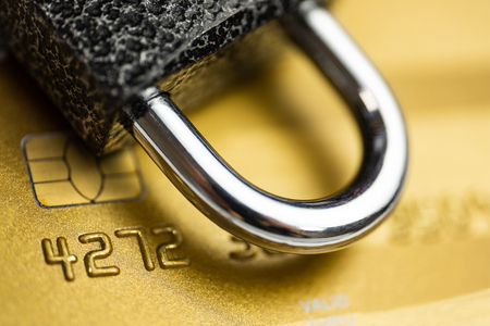 Concept of security payment. Lock on gold credit card. Close up.