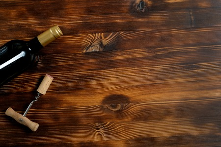 A dark bottle of wine next to a corkscrew and a twisted cork on a wooden background. Top view with copy space.
