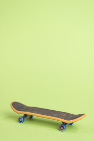 Fingerboard on a green background in the center. Close up with copy space. Vertical.