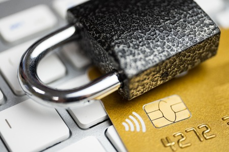 Concept of security of electronic payment. Lock on gold credit card and white keyboard. Close up.