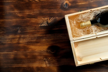 A dark expensive bottle of wine in a wooden box on a wooden background. Top view with copy space. Close up. 스톡 콘텐츠