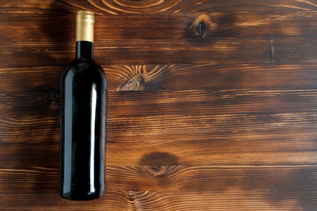 A dark bottle of wine on a wooden background. Top view with copy space.