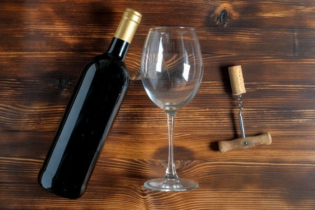 A dark bottle of wine next to a corkscrew and a twisted cork , glass goblet in the center on a wooden background. Top view with copy space.