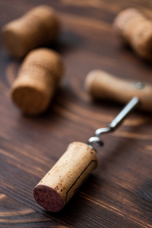 Corkscrew and corks on a wooden background. Close up. Vertical.