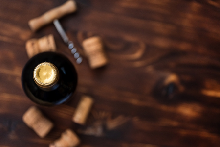 A dark bottle of wine next to blurry a corkscrew and corks on a wooden background. Top view with copy space. Stock Photo