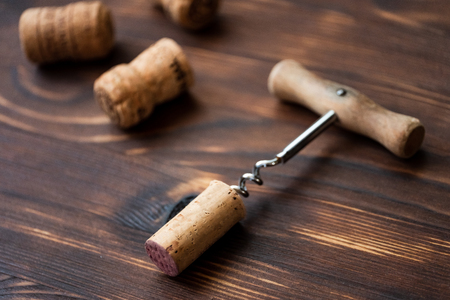 Corkscrew and corks on a wooden background. Close up.