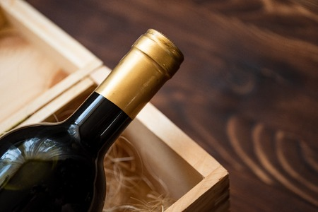 A dark expensive bottle of wine in a wooden box on a wooden background. Close up.