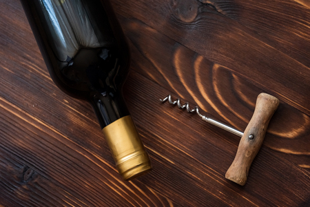A dark bottle of wine next to a corkscrew on a wooden background. Top view.