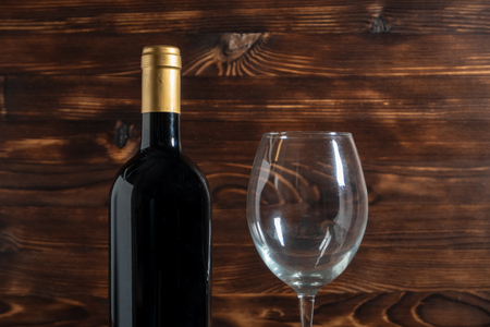 A dark bottle of wine next to glass goblet in the center on a wooden background.