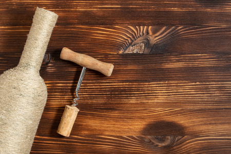 A bottle of home wine next to a corkscrew and a twisted cork on a wooden background. Top view with copy space. 스톡 콘텐츠