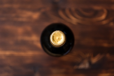 A dark bottle of wine blurry on a wooden background. Top view.