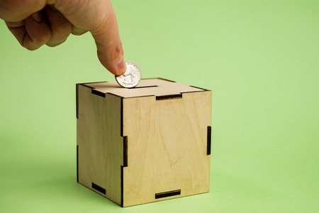 Hand depositing coin of dollar bill into moneybox on the green background.
