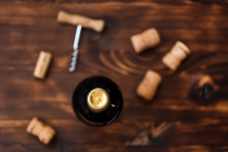 A dark bottle of wine next to blurry a corkscrew and corks in the center on a wooden background. Top view. 스톡 콘텐츠