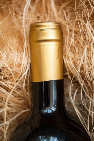 A dark bottle of wine on a hay background. Top view. Close up. 스톡 콘텐츠