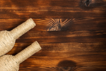 A bottle of home wine on wooden background. Top view with copy space.