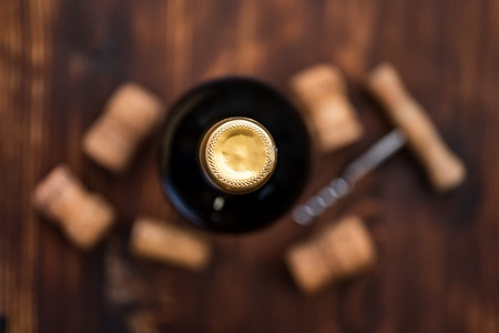 A dark bottle of wine next to blurry a corkscrew and corks at center on a wooden background. Top view.