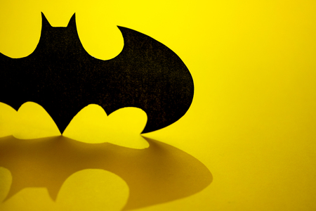 RUSSIA, ST.PETERSBURG, April 16, 2019: DC comics batman sign black logo printed with shadow on yellow background 에디토리얼