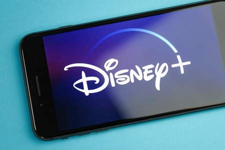 RUSSIA, ST.PETERSBURG, April 16, 2019: Image Disney plus on a smartphone on a blue background. Close up Editorial