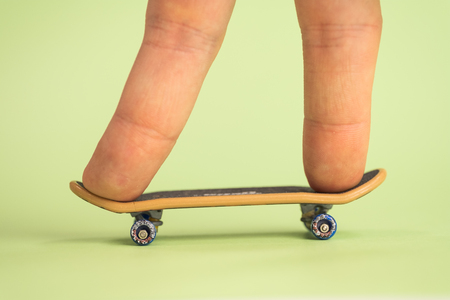 Fingerboard. Man hoplding by two fingers small skateboard on green background. Close up.