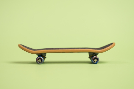 Fingerboard on a green background in the center. Close up.