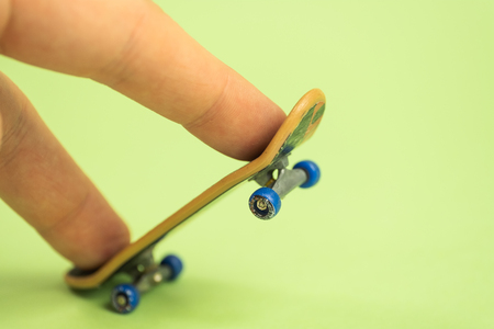 Fingerboard. Man playing by two fingers with small skateboard on green background. Close up. 스톡 콘텐츠