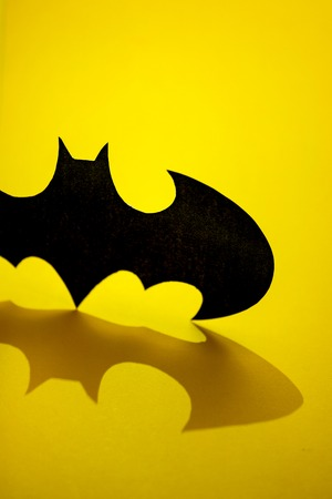 RUSSIA, ST.PETERSBURG, April 16, 2019: DC comics batman sign black logo printed with shadow on yellow background. Vertical.