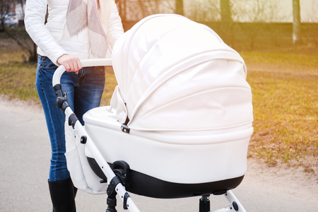 Woman in white in white jacket, blue jeans and grey scarf strolling with white baby-carriage. Flare.