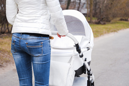 Woman in white jacket and blue jeans strolling with white baby-carriage. Rear view. 스톡 콘텐츠