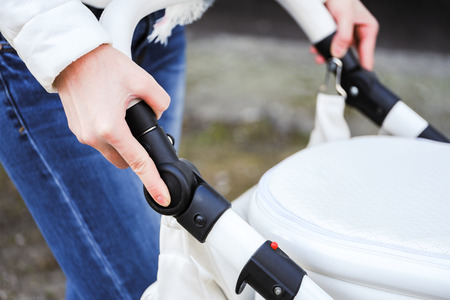 Woman strolling with white baby-carriage. Close up of female hands push the button to change position adjustable handle white baby-carriage. 스톡 콘텐츠