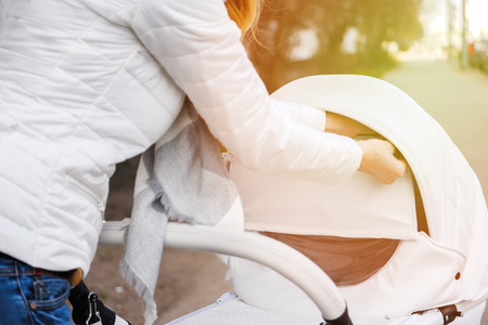 Woman strolling with white baby-carriage. Female hands close modular pop-up white baby-carriage to raise wind protection. Flare.