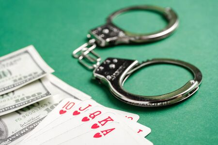 Handcuffs lie next to playing cards and US dollars on a green background. Gambling crime concept. Close up.