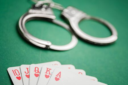 Handcuffs lie next to playing cards on a green background. Gambling crime concept. Close up.