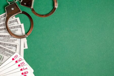 Handcuffs lie next to playing cards and US dollars on a green background. Gambling crime concept. Copyspace.