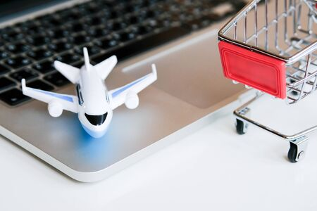 A model airplane stands on a laptop next to a trolley. The concept of buying tickets for a flight through the Internet. Close up. Foto de archivo - 134556099