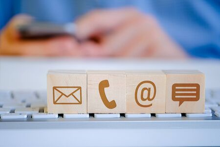 A man holds a smartphone with his hands, in the foreground there are wooden cubes with letters, email, phone and message icons. The concept of viewing content. Close up. Foto de archivo - 134556100