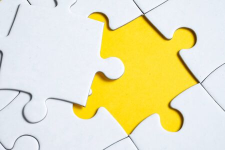 Missing white piece lies on jigsaw puzzle on yellow background. Concept of completing the final puzzle piece, achieving goal.
