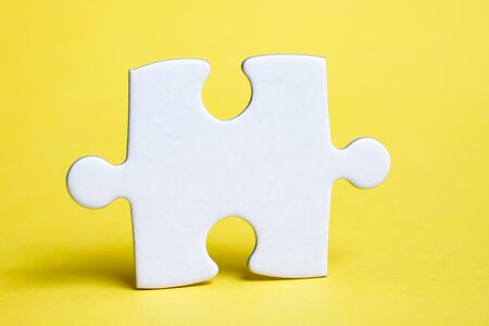 A piece of white puzzle on a yellow background. The concept of the necessary details for the task. Close up. Foto de archivo - 135094087