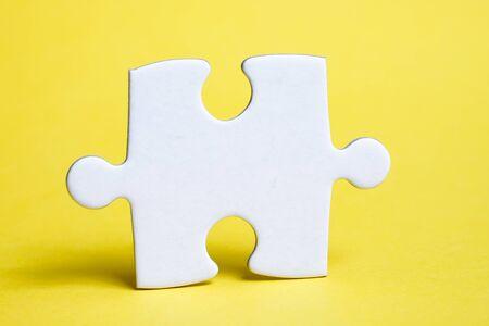 Ein Stück weißes Puzzle auf gelbem Grund. Das Konzept der notwendigen Details für die Aufgabe. Nahaufnahme.