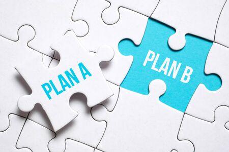 Notfallplankonzept. Ein Puzzleteil mit der Aufschrift hält die Finger eines Mannes neben einem anderen auf blauem Grund. Nahaufnahme. Standard-Bild