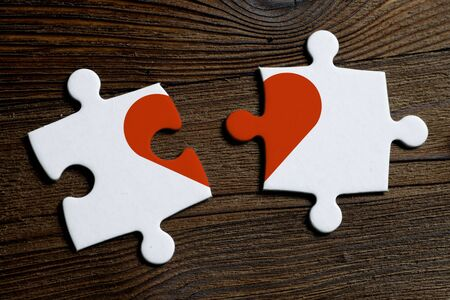 The concept of parting and not mutual love. Pieces of a white puzzle on a wooden background. Close up. Banco de Imagens