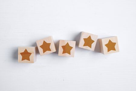 Five stars on wooden blocks showing the best rating. Best score. Flat lay. Close up.