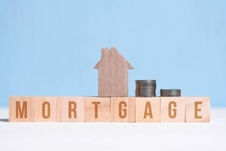 Cardboard cutout house and coins on cubes with inscription mortgage on blue background.