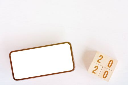 Mock up of smartphone, wooden cubes with numbers symbolizing new year 2020 on white background with copy space. Toned. Foto de archivo - 134556358