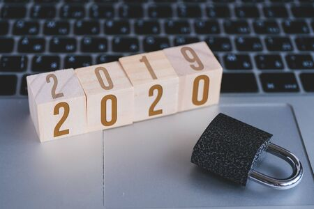 Padlock and cubes with numbers symbolizing new year 2020 standing on keyboard of open laptop. Concept of computer security. Foto de archivo - 134556375