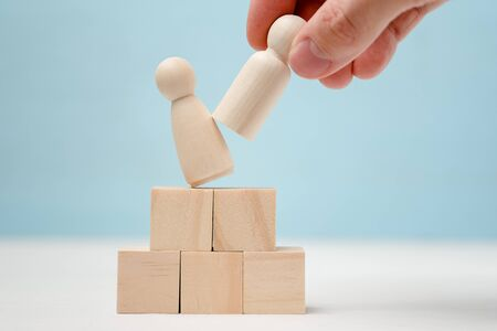 Male hand puts wooden figure on podium shifting the figure standing there. Consept of director replacement.