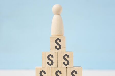 The abstract wooden figure of man on toy blocks with painted dollar signs on blue background. Concept of wealth.